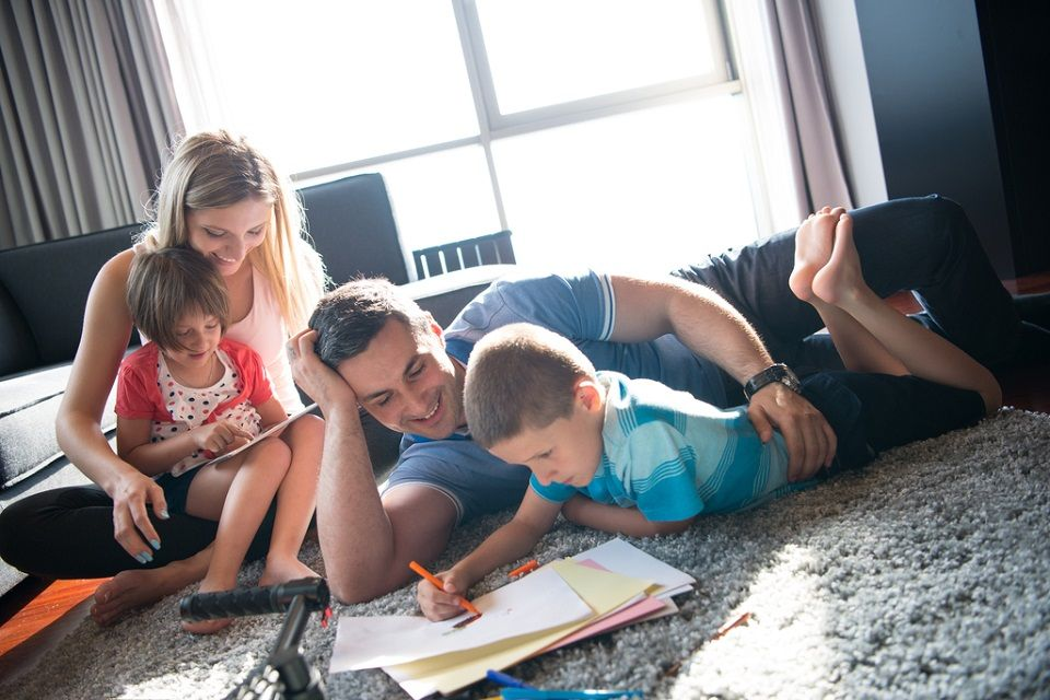 family on carpet doing homework